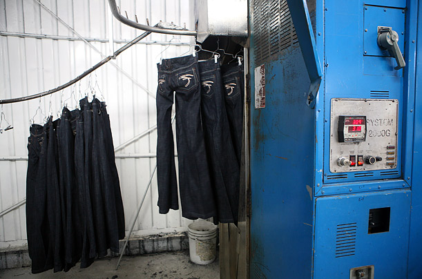 Jeans hang on a conveyor belt leading to an oven that will bake them to a worn look at All American Wash.