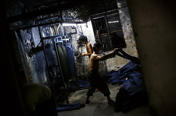 A worker uses a sanding machine to distress jeans. The factory also scrubs, sprays, tears and stone-washes their products.