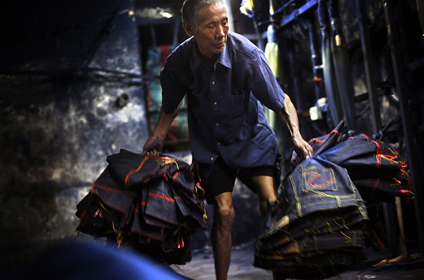 A worker carries finished jeans off of the factory floor. The Chinese boomtown is home to 5,000 garment makers.